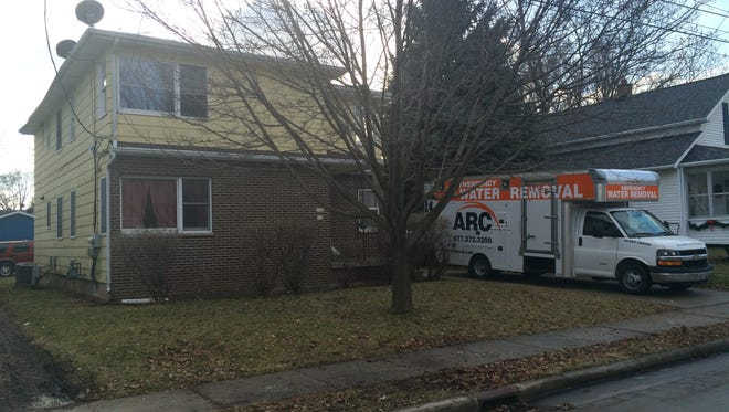 Crews from ARC Contracting clean up after an early-morning fire damaged an upstairs bedroom in a two-story duplex Friday, Dec. 26, 2014, in the 900 block of Bismarck Avenue in Oshkosh.