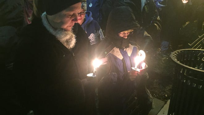 Sandy Arnold and her son Austin, hold candles at the vigil in Covington to honor fallen police officers.