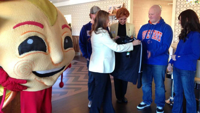 Hayden Adkins, center, receives a Fiesta Bowl jacket from Kimberly Trichel while his brother Jaron Adkins looks on with the Graduate Hotel's Pat Warren, left, and Make-A-Wish Arizona's Shoshana Simones