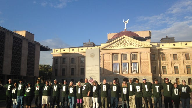 """Protesters for marijuana reform and legalization wear shirts that spell out """"End cannabis prohibition"""" in front of the state capitol Monday."""