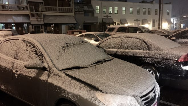 Snow covers cars in a downtown Franklin parking lot.