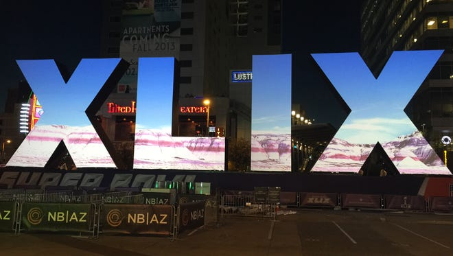 The Super Bowl XLIX logo at Super Bowl Central in downtown Phoenix lights up at night and rotates through graphics.