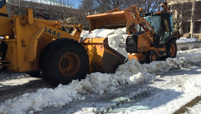 Work crews clear snow from Central Avenue in Staunton on Monday.