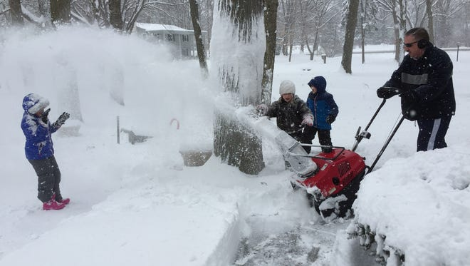 Allison Brady, 9, Indianapolis, enjoys the blast of snow from her father Peter Brady's snowblower as he clears their sidewalk on Nottingham Drive, just west of Westfield Boulevard on the Northside after about 10 inches of snow fell overnight on Sunday, March 1, 2015. Their next-door neighbor and friend Gabby Deer, 8, and Allison's brother, Alex, watch from behind a tree.