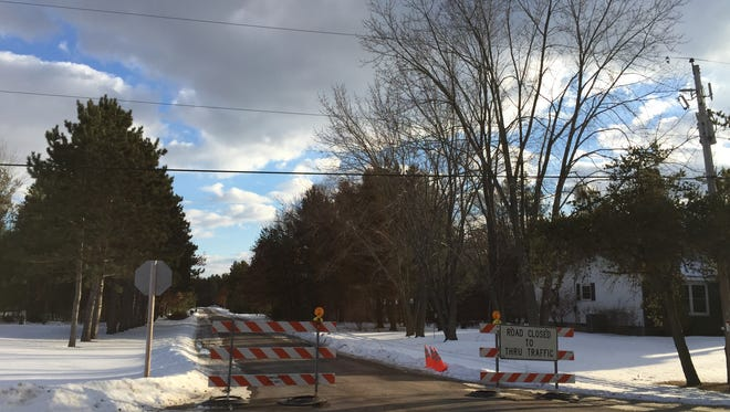 Traffic barriers block Larry's Drive on Saturday in Hull, near the home where two bodies were found Friday.