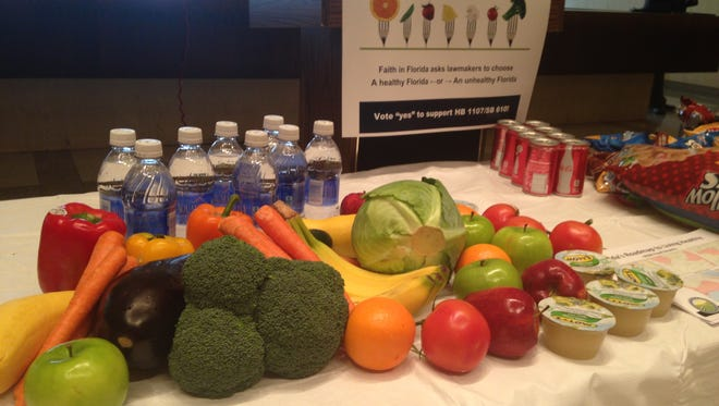 During a Thursday press conference at the Capitol, a table displayed healthy foods to stress the need reduce food deserts. A bill has been proposed to offer tax credits to qualified businesses as an incentive offering healthy foods.