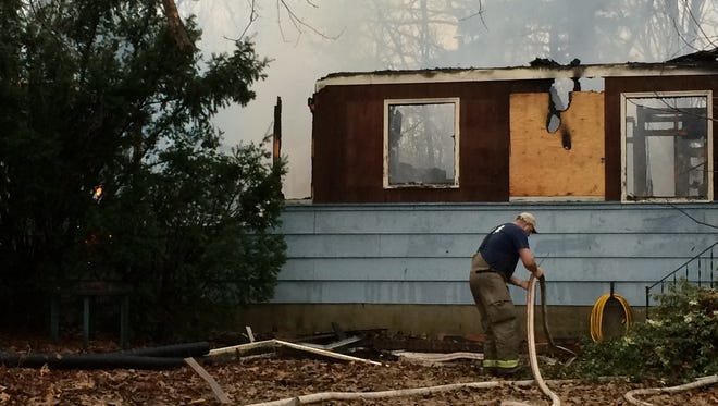 A firefighter breaks down a hose after fighting an early morning fire on Deer Hill Lane in Swoope that killed two Friday.