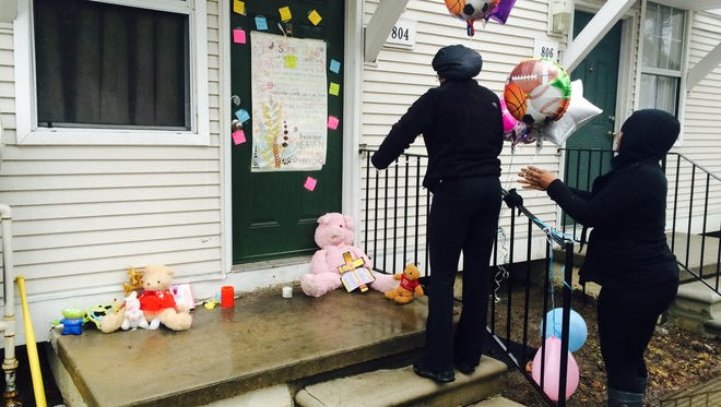 Toni Williams, 28, left, and Natasha Bell, 30, leave balloons March 25, 2015, at the town home in the Martin Luther King Apartments in Detroit where two children were found dead in a freezer.
