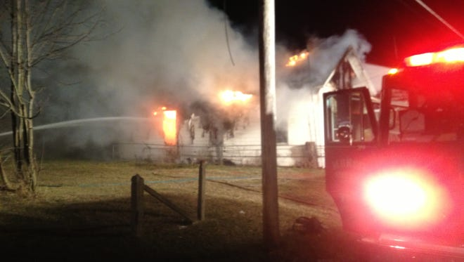 Firefighters battle a house blaze at 521 W. Sixth St. early Saturday.