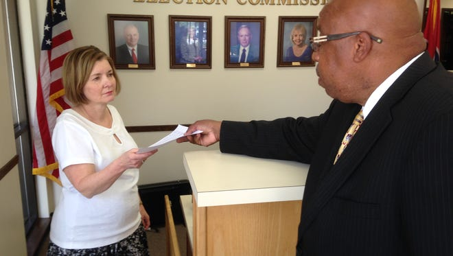 James Baxter presents Kim Buckley with papers at the Madison County Election Commission
