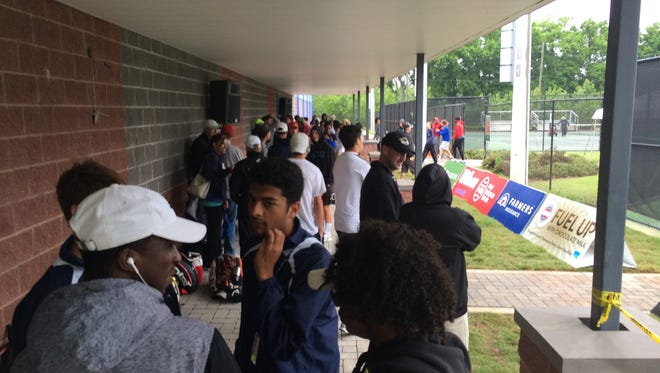 Tennis athletes and coaches gather under an awning at Old Fort Park while waiting for courts to dry to begin individual championships Thursday morning.