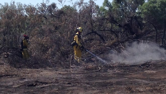 A Cal Fire firefighter puts out a hot spot at the scene of the Harrison Fire in Thermal Tuesday. Full containment is expected Friday.