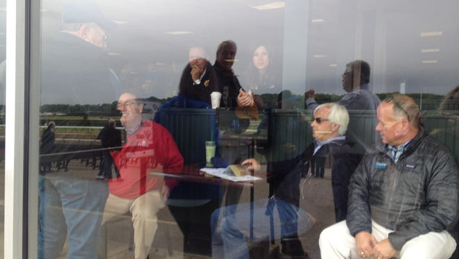 As shot through the glass in front of part of the trackside clubhouse where trainers often watch their horses, Kiaran McLaughlin (sitting at left) talked with Bob Baffert the day before the Belmont Stakes.