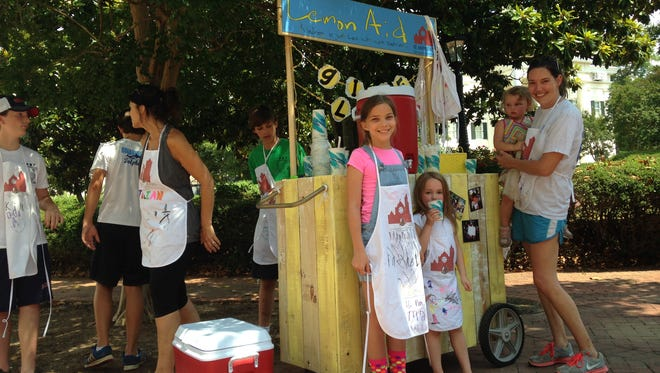 """Maggie Sewell, Tinsley Ferris, Sidney Ferris, and Metta Margaret Ferris with St. Andrew's Episcopal Church hand out free """"lemonaid"""" in downtown Jackson Thursday afternoon."""