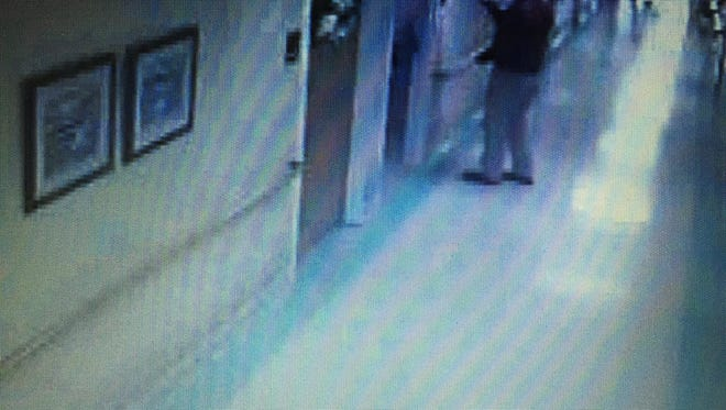 Clayton Kelly shown in surveillance footage from Easter Sunday 2014 taking a photo of the name plate outside the late Rose Cochran's nursing home room.