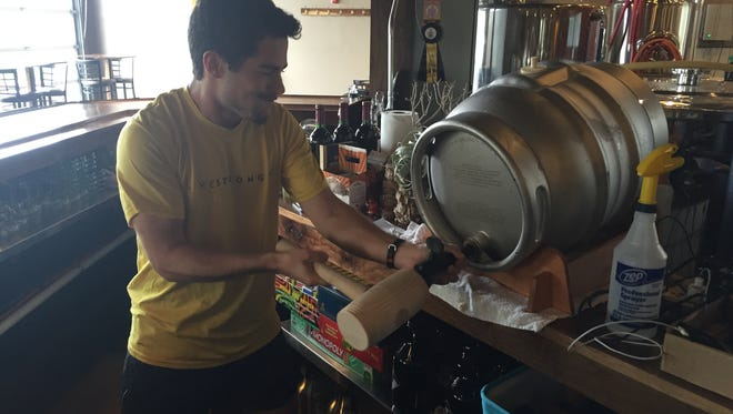 Sam Meehan, the brother of Swiftwater co-brewer Pat Meehan, taps a cask of Sweet Cherry Brown Ale on Wednesday at the South Wedge brewery.