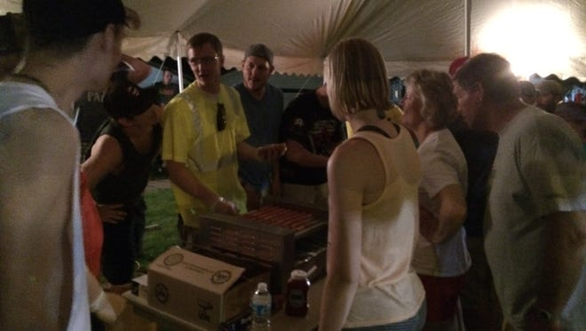 Tim Miller, center, slowly cooking hot dogs