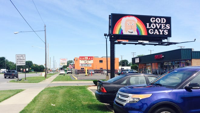 """A """"God Loves Gays"""" sign on a billboard seen Wednesday on the 6800 block of Telegraph in Dearborn Heights contrasts a more judgmental sign previously seen here."""