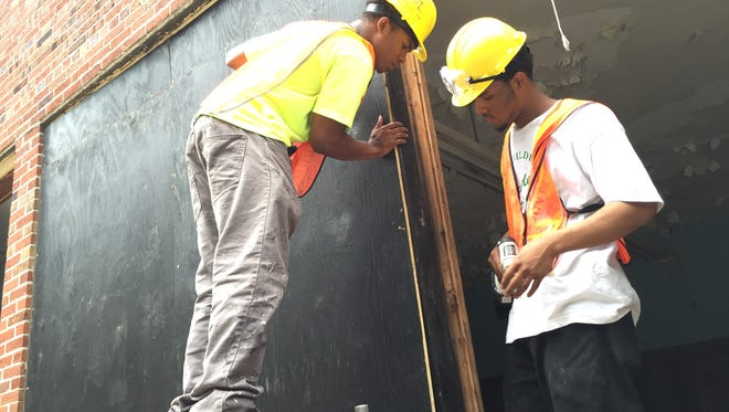 Armani Bell, 18, at left, and Anthony Samuels, 19, put in place the boards that will cover windows at the vacant Holcomb Elementary School on Detroit's northwest side on Tuesday, June 30, 2015.