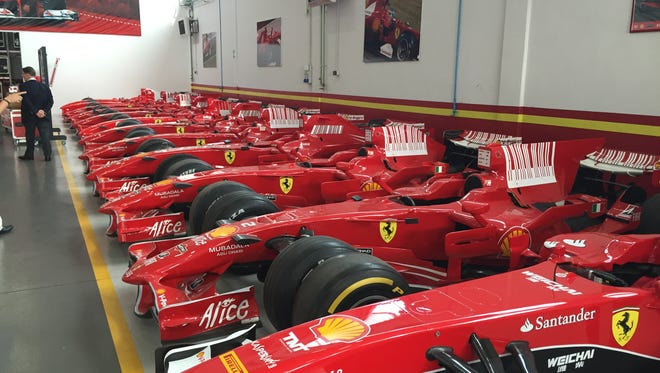 A row of Formula 1 race cars that are either for sale or have been purchased sit in storage for their owners.