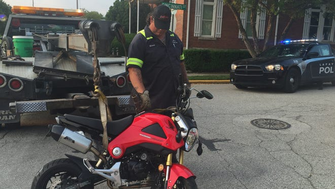 Michael Bradbury of Jim's Garage in Lafayette prepares a damaged Honda motorcycle for towing Saturday, July 4, after a crash sent the driver to the hospital.