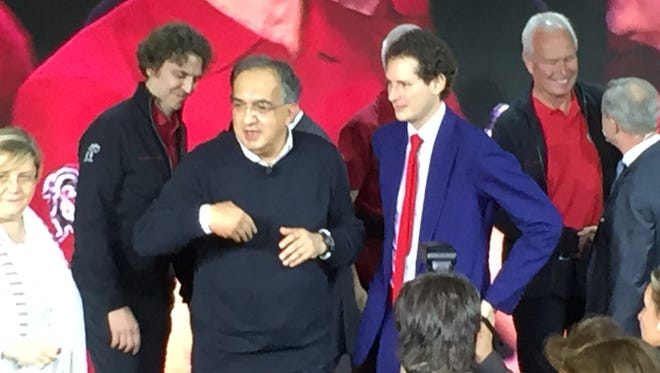 Fiat Chrysler CEO Sergio Marchionne, left; and Chairman John Elkann, right in blue suit, celebrate reveal of Alfa Romeo Giulia in Milan on June 24, 2015.