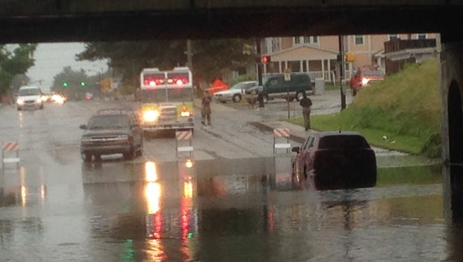 Rescue crews help a driver stuck in flooding in the Madison Street underpass after heavy rain on Tuesday, July 7, 2015.