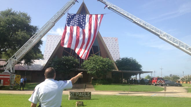 Shreveport Assistant Chief David Dice makes sure the flag is straight at St Paul's for the funeral of Virginia Shehee.