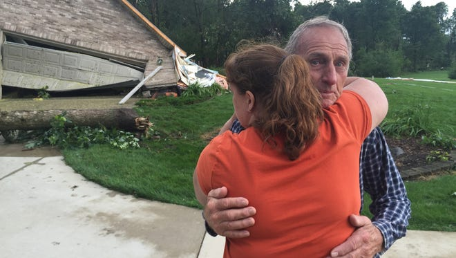 Colette Eversole hugs neighbor Clyde Roberts after his garage and many trees were damaged by what Robert said with a tornado on Friday, July 17, 2015.
