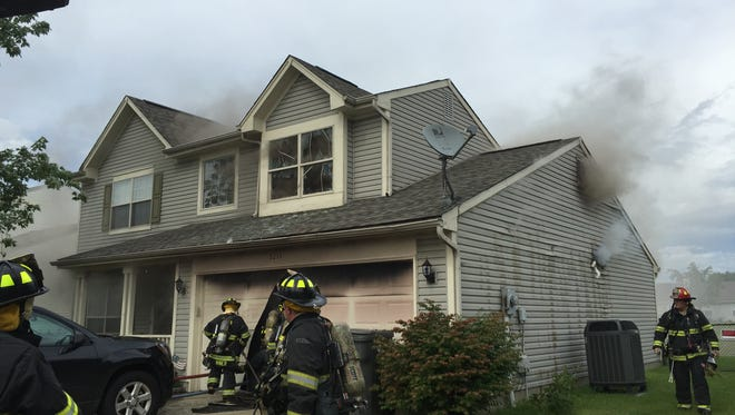 Firefighters walk around the house, on the 5200 block of Thompson Park Blvd.