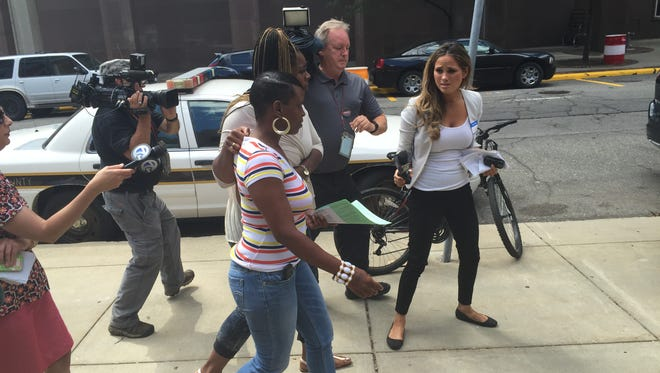 Kwanna Luchie, mother of the 11-year-old boy now facing manslaughter charges, leaves the Juvenile Detention Center in downtown Detroit while surrounded by reporters.