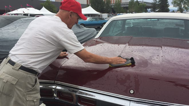 Buck Brokofsky of Medford, Ore., wipes the rain from his 1969 Chevy Caprice in the parking lot of the Grand Sierra Resort on Friday morning. Rain or shine, Hot August Nights continues through Sunday.