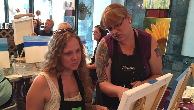 Liz Hernandez, left, gets advise from paint instructor Kristen Woolley.