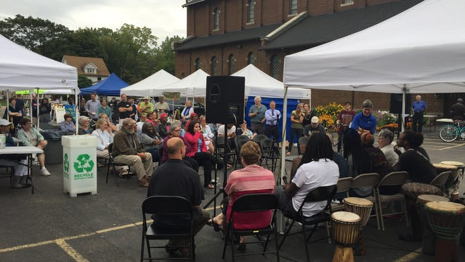A community panel discusses the intersection of violence and health at the Westside Farmers Market in the parking lot of St. Monica Church on Genesee Street on Tuesday.