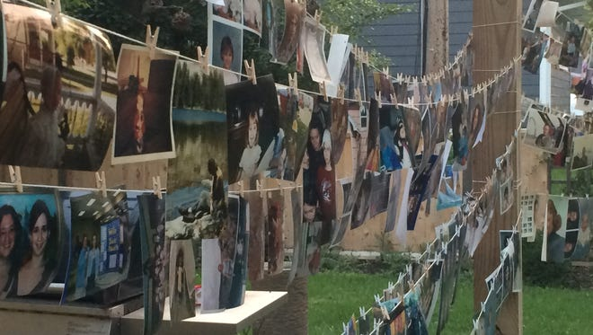 Photos hang out to dry in Suzi Brude's backyard in Sioux Falls. The photos had been caked in mud after Thursday's storm flooded the basement where they were kept.