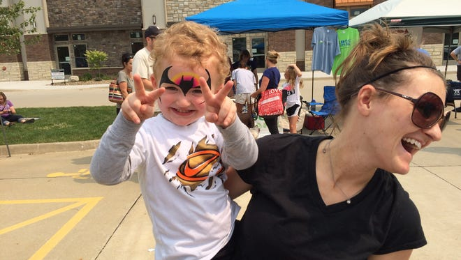 Brecken Scharf does his best Batman impression with his mother, Amber Scharf, at a North Liberty block party celebrating the end of construction on Highway 965.