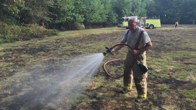 Parsippany firefighters spread water on a brush fire on a Brooklawn Middle School field Wednesday in Parsippany.