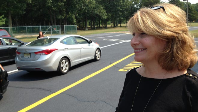 Suzanne Bruno, head of school at Calvary Academy, a private school in Lakewood, greets parents waiting to pick up their children on Sept. 3. The school learned later that day that  about 50 of its students would receive busing, after being told earlier in the week that no routes were available.