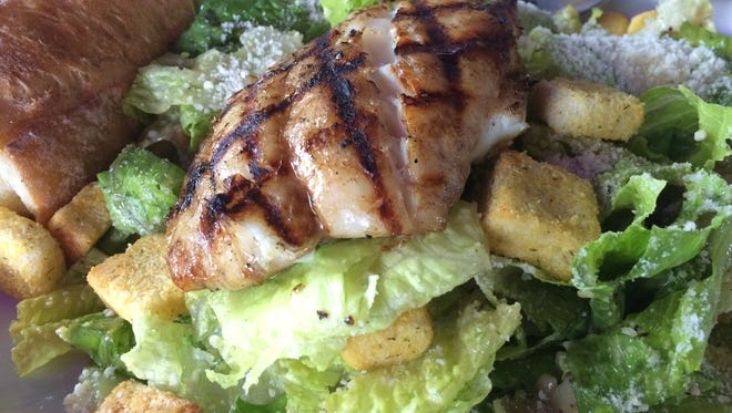 A Caesar salad topped with chargrilled grouper from Lazy Flamingo.