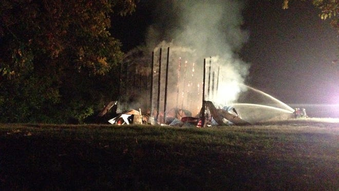 Woodlawn Volunteer Fire Department personnel battle a Saturday night blaze at a tobacco barn on Coleman Road.