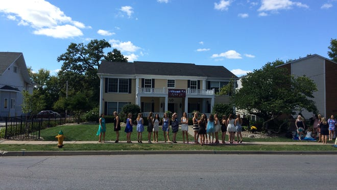 Women stand outside the Alpha Phi sorority at Drake University, where police apprehended a suspect in an armed robbery Saturday.