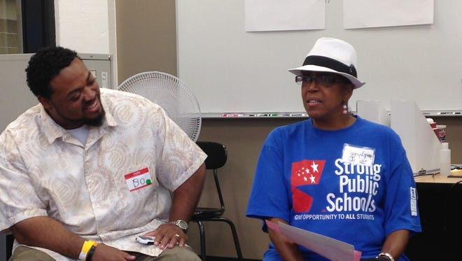 Mary Lynn Jones, a retired central office staffer for the Des Moines public schools, helps lead a small-group discussion after a larger forum sponsored by the teachers' union. Listening in is parent and activist Bo James.