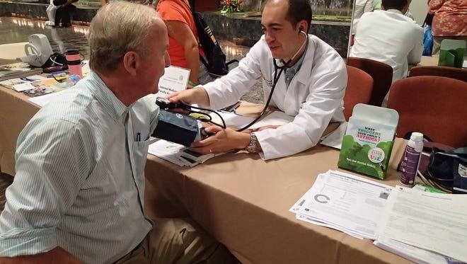 Congressman Rodney Frelinghuysen getting a blood pressure screening from an Atlantic Health System doctor.