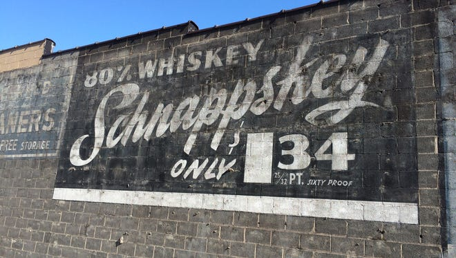"A recently exposed advertisement on the Detroit border in Grosse Pointe Farms can be seen at at Mack and McKinley avenues. The black-and-white image on cinder blocks features ""Schnappskey,"" a whiskey for $1.34 per 25/32 pint."