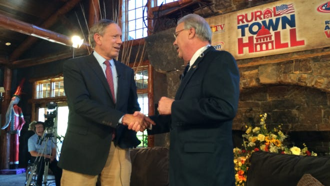 Former New York Gov. George Pataki shakes hands with television host, Mark Oppold at the Stine Farm in West Des Moines Saturday afternoon.