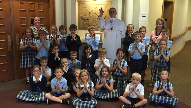 Second grade students at St, Francis de Sales School pose with a cardboard cut-out of Pope Francis. The school spent this week celebrating his visit.