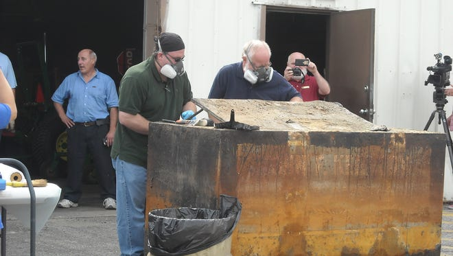 Bay County officials open the county's time capsule on Thursday. The majority of the materials were likely lost due to water that seeped in over decades.
