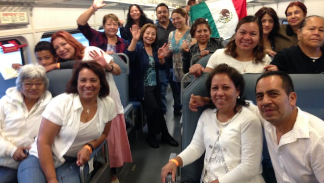Parishioners of St. Monica Roman Catholic Church, Atlantic City, aboard the express train to Philadelphia Saturday. Among them are immigrants from Mexico, Colombia, Honduras, the Dominican Republic and Peru.