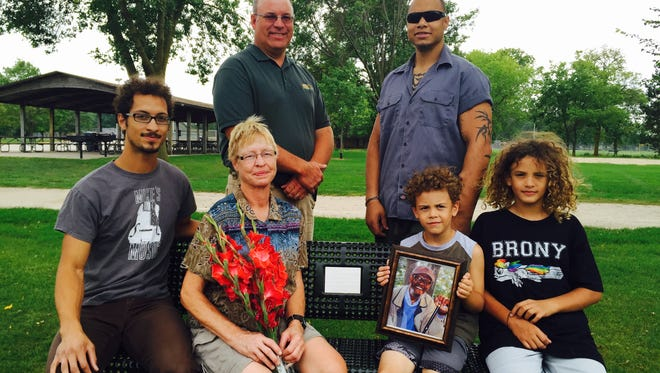 The family of the late Ishamon Harris Jr. sits on a park bench dedicated in his memory at Lakeside Park in Fond du Lac. Front row, from Left: Levi Harris, Barb Harris, Guardian Harris and Shaman Harris. Second row: City o Fond du Lac Parks Director John Redmond and Ian  Harris.