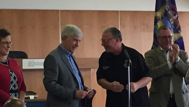 Gov. Rick Snyder, left, speaks with River Rouge Mayor Michael Bowdler at event to announce new program to help economically struggling cities. Monday, Sept. 28, 2015
